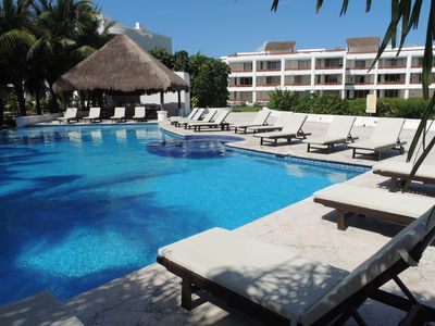 The beach pool with plenty of comfortable lounge chairs and covered seating.