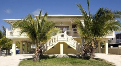 Front, 4 palm trees with coconuts and double staircase
