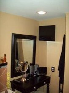 Vanity area and flat screen TV viewable from jetted double tub