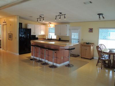 5 bar stools surround the kitchen island