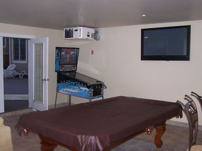 Game room with pool table, pinball machine, big screen tv, bar and furnishings