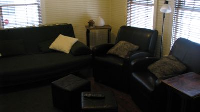 Couch, 2 chairs and hassocks and side tables in living room