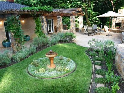 Beautiful landscaping & flagstone patio with outdoor dining & fireplace