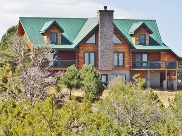 Williams cabin rental - View of the house as you enter the property. Decks have expansive views north.
