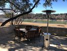 Stone patio with propane heater, large table, lights and gas grill