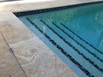 New pool with glass tile and travetine marble patio