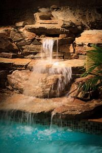 a waterfalls is carved out of the landscaping cascades into the pool.