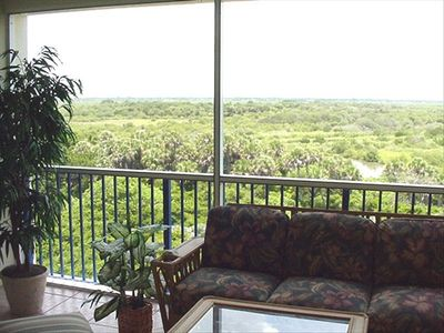 Screened balcony with beautiful furniture overlooking the wetlands.