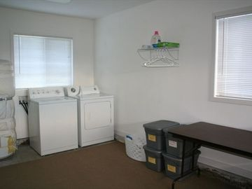 Bright laundry room. Ironing board, recycle receptacles and folding table.