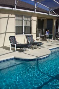 Spacious pool deck and covered lanai with fan