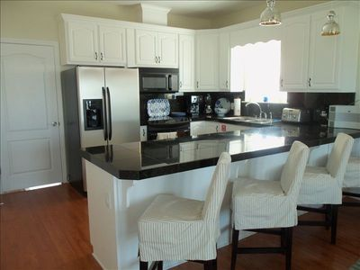 Gourmet kitchen with granite counter tops, professional decor.