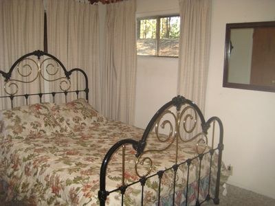 Second bedroom w/queen bed view of forest, vhs player w/collection of movies, ec