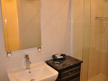 Bathroom features a large tiled shower stall with rain shower head.