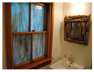 Newport house photo - Slag glass and driftwood mirror by local artist complement the Spring Bathroom