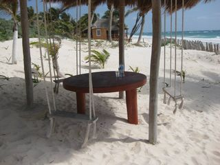 Tulum house photo - Great beach table with swing chairs with a grass roof for shade.