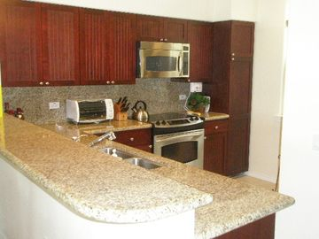Kitchen with SS appliances, granite counters,& a Double Door SS GE Refrigerator.