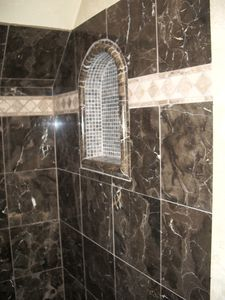Large shower tiled with emperador marble.