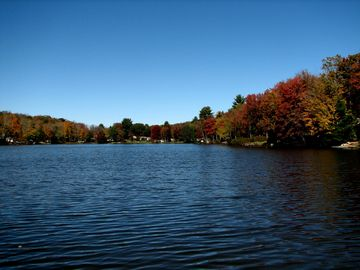 The forest surounding the lake explodes with color in the Fall.
