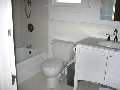 Bathrooms updated in white mosaic or subway tile with modern fixtures