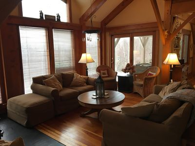 Sunroom adjoins deck & dining room with comfortable seating and gas fireplace.