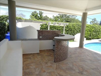 Outdoor shower and bar area with the BBQ just beyond, beside the pool