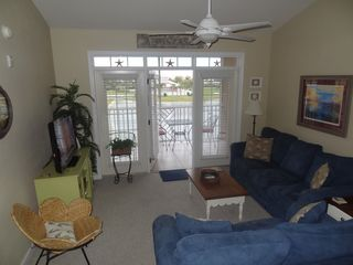 St. Augustine Beach condo photo - Living room with cathedral ceiling and door to screened balcony.
