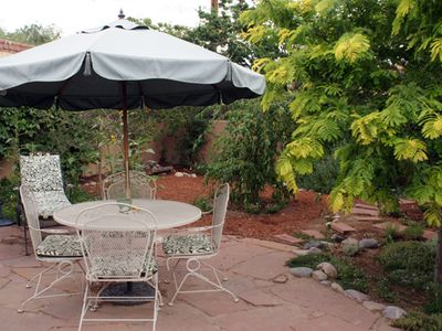 Back patio retreat with greenery, umbrella table and lounge chair