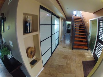 Entry with open floor plan, travertine and wood floors on first story.