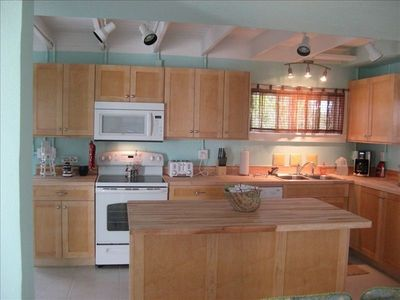 Well equipped kitchen with butcher block countertops and new appliances