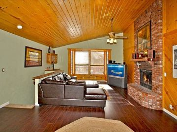 Upstairs living room with wood fireplace, knotty pine vaulted ceiling, mtn view