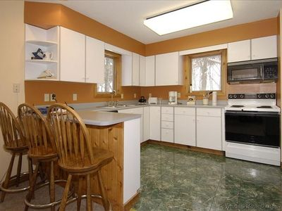 Warm kitchen with full amenities right next to 10 seat Dining Room table