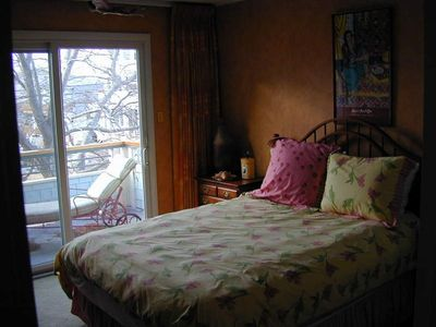 2nd bedroom has balcony overlooking bay, queen bed