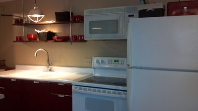 full kitchen, newly remodeled, complete with microwave, stove, oven, and fridge