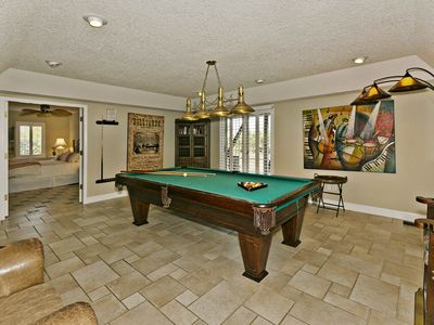 Game room with pool table, tv and small fridge.