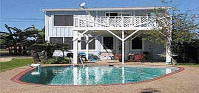 View from small pier on canal, Palacios Bay two-story home with deck and pool.