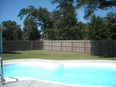 Large fenced back yard with in-ground pool and surrounded by live oaks
