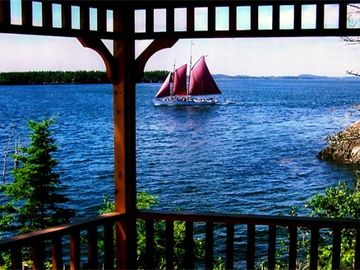 Sailboat passes by the screened in gazebo
