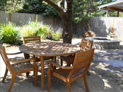 Private, fenced backyard with a large firepit and table/chair set.