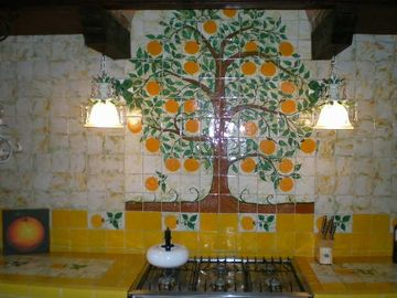 Open kitchen has tile wall art of orange tree in front courtya