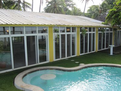 house with all glass overlooking pool near large patio under trees for cooling.