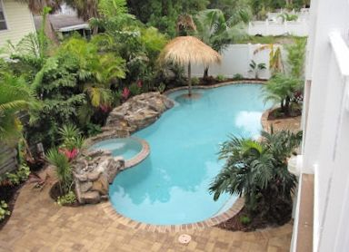 View of pool w/ hot-tub & in-pool tiki table, lush and tropical landscaping