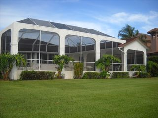Vacation Homes in Marco Island house photo - Manicured ground with ample greens and large lanai.