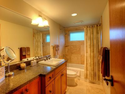 Main hallway bathroom finished in natural stone and cherry cabinets