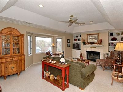 Warm and Cozy Living Room Features Large Windows and Gas Log Fireplace