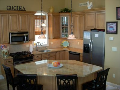 Kitchen with granite counters and granite island that seats 4