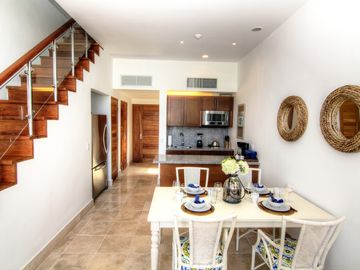 View of dining area, kitchen and stairs to bedroom