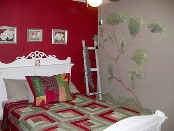 "The ""Stardust Way"" Red Bedroom is cozy with a Queen Bed."