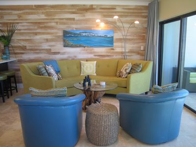 Living room w steel-brushed wood wall accent. Upscale & cozy furnishings.