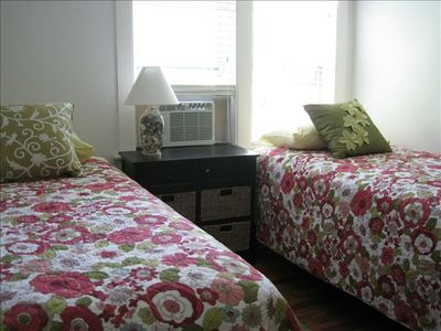 The upstairs children's room with 2 twin beds, a side table and a dresser