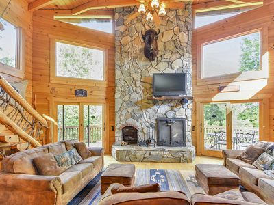 Spacious great room features large stone fire place & plenty of seating.